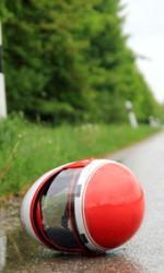 Motorradhelm auf Fahrbahn horizontal